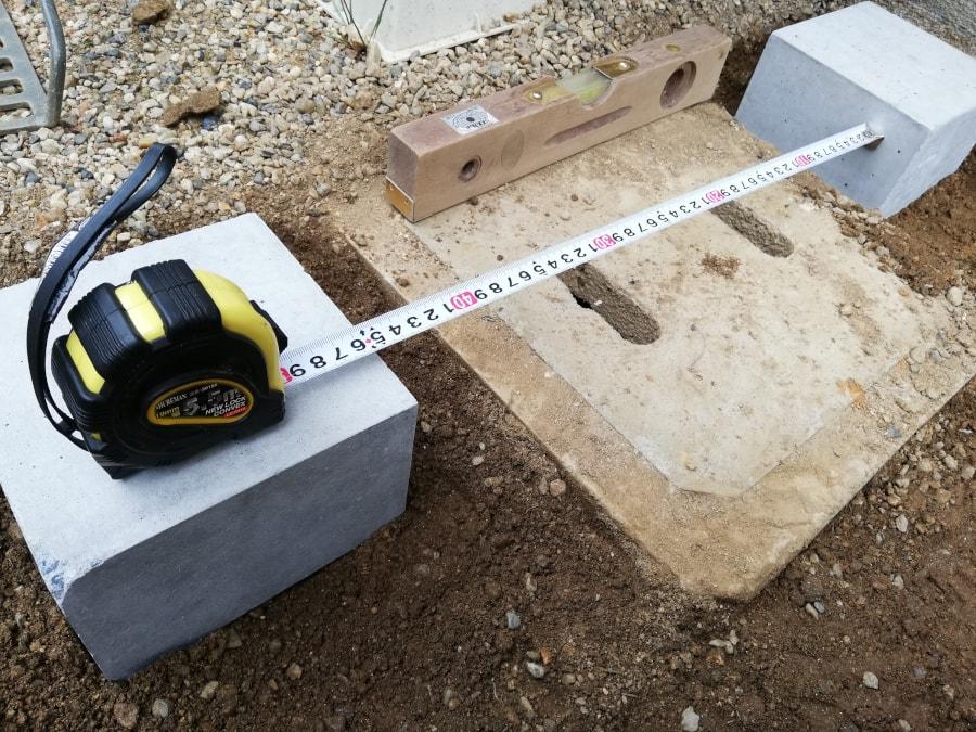 束石同士の距離をメジャーで測りながら束石を置いていく